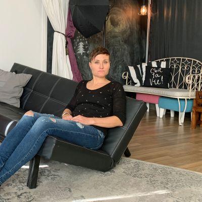 Heidi Noponen istuu risalla sohvalla