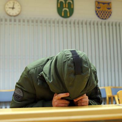 Man sitter vid ett bord i en grön rock, med huvan dragen framför ansiktet.