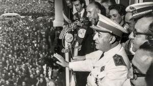 Spaniens framlidna diktator Francisco Franco står omgiven av personer på en balkong, i bildens vänstermiljö syns en stor folkmassa.