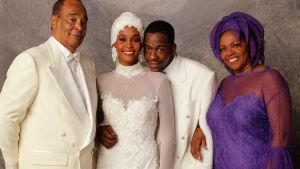 Whitney och Bobby Brown fotograferade på bröllopet tillsammans med Whitneys föräldrar.
