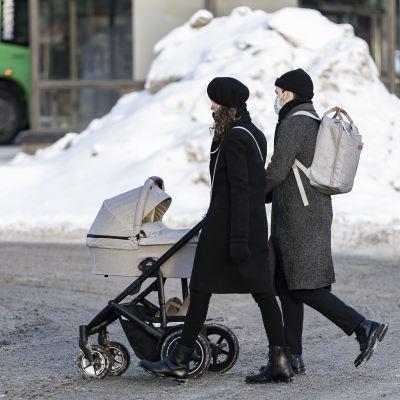 Ett par går med barnvagn på en snöig gata i Hagnäs i Helsingfors.