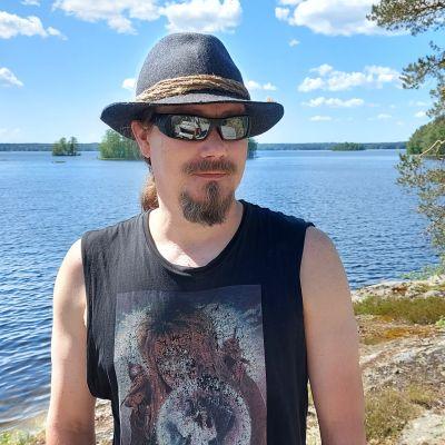 Tuomas Holopainen seisoo järvenrantamaisemassa