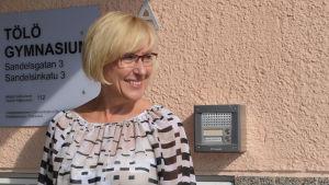 Marina Sjöholm står vid skylt där det står Tölö gymnasium.