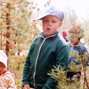 Pieni lippalakkinen poika marjametsässä tarhakavereiden kanssa.