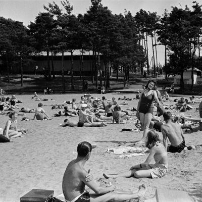 Mustavalkokuva ihmisistä istumassa Hietarannan uimarannalla. Keskellä nainen poseeraa seisaaltaan kameralle. Taustalla puiden takana Hietaniemen paviljonki.