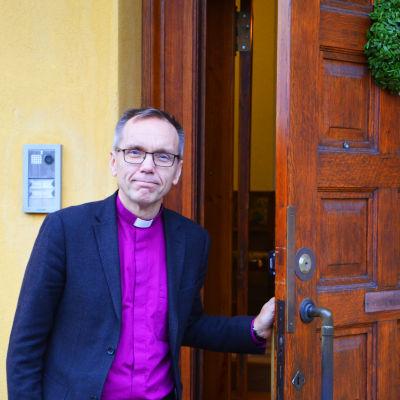 En man står utomhus och håller upp en ytterdörr.