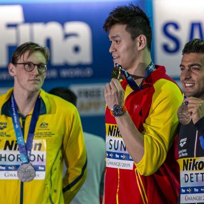 Sun Yang och Gabriele Detti poserar med sina medaljer, medan Mack Horton stirrar på Yang.