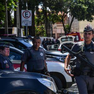 Poliser utanför en skola i Suzano i närheten av São Paulo, där en gärningsman sköt ihjäl flera personer.