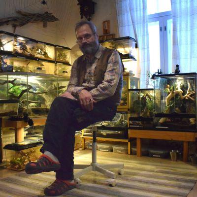 Richard Donner sitter mitt bland sina terrarier i ett vanligt rum.