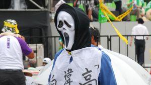 Taiwanesisk demonstration. Person iklädd skrämmande mask deltar.