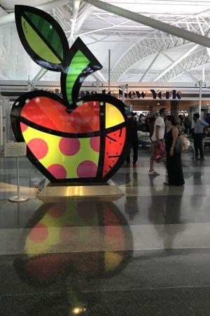 Flygturisten möts av en glasstaty av det stora äpplet, New Yorks symbol, på JFK-flygfältet