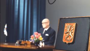 Presidentti Urho Kekkosen uudenvuodenpuhe 1.1.1969. Presidentin vaakuna kuvassa tarkka. Presidentti kuvassa taustalla.