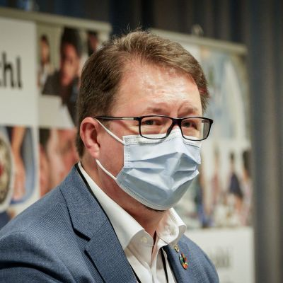 Mika Salminen iförd munskydd under en presskonferens.