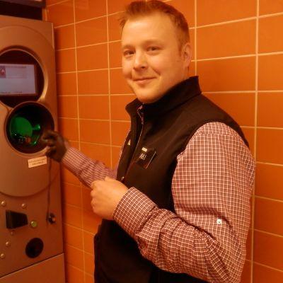 Köpman Aki Salminen visar hur det går till när man lurar flaskautomaten