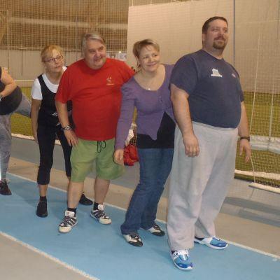 Seitsemän kävelijää urheiluhallissa.