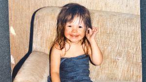 Sonja Kailassaari som liten, nybadad med en blå handuk omkring sig i soffan.
