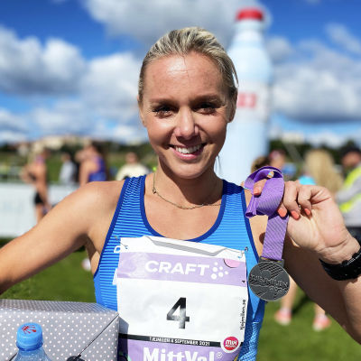 Nina Chydenius poserar med en present i ena handen och en medalj i den andra. Hon ler.