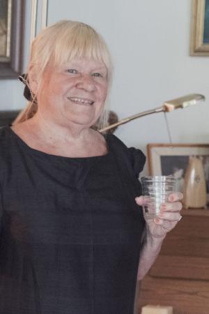 Maritta Pellava pianonsa edessä vesilasi kädessään.