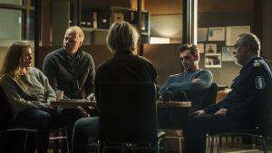 Rikostutkijat istuvat tuoleillaan pyöreän pöydän ääressä.