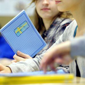 Tre skolelever sitter i pulpeter. En tjej håller i ett häfte med Sveriges flagga.