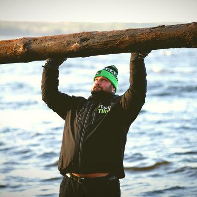 Mika Törrö lyfter en stock över huvudet på stranden