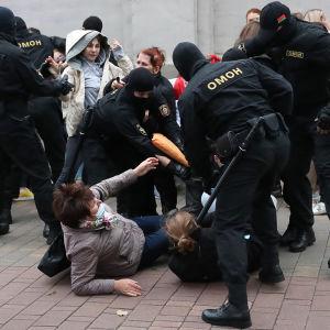 Mielenosoittajia makuullaan maassa ympärillään poliisin erikoisjoukkoja