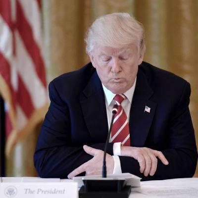 Donald Trump sitter vid ett bord med en mikrofon framför sig, med händerna knäppta och blicken vänd nedåt.