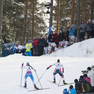 Marit Björgen rycker iväg från Krista Pärmäkoski, VM-skiathlon, 2017.
