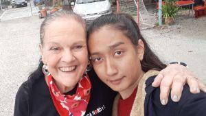 En leende medelålders kvinna håller om ett barn.