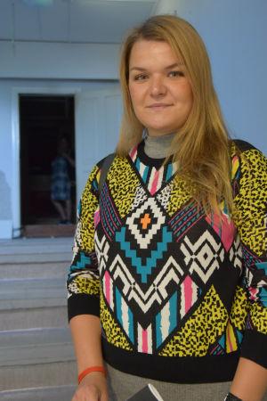 Kvinna med färggrann tröja ser in i kameran.