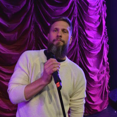 Magnus Betner tittar in i kameran med en mikrofon i handen.