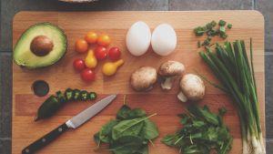 Grönsaker och ett par ägg på ett skärbräde av trä