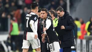 Cristiano Ronaldo springer bort från planen och håller på att beröra Paulo Dybalas hand.