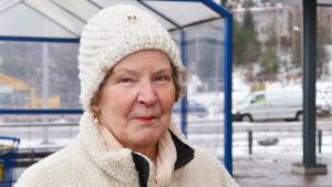 En äldre dam står utanför en mataffär.