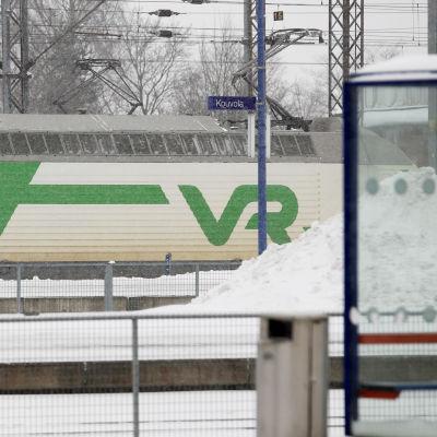 Tåg åker förbi snöig tågstation