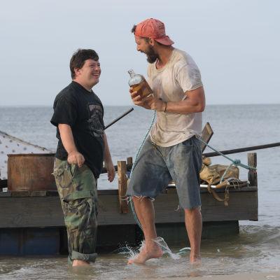 Zak (Zack Gottsagen) och Tyler (Shia LaBeouf) står vid en flotte, de håller i en whiskeyflaska och skrattar.