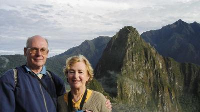 Peje och Pearl vid Machu Picchu. Båda ler mot kameran och har spetsiga berg i bakgrunden.