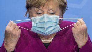 Förbundskansler Angela Merkel tar bort sitt munskydd för att hålla presskonferens 14.10.2020.