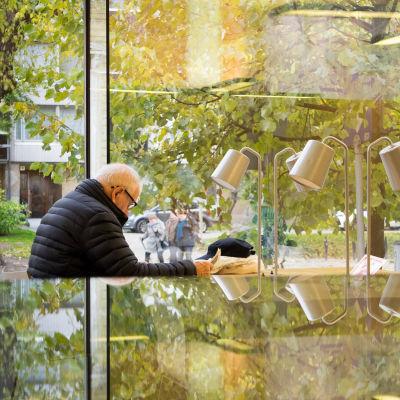 Vanhempi mies lukee sanomalehteä kirjastossa