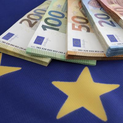 Eurosedlar (200, 100, 50, 20 och 10) fotograferade på en EU-flagga.