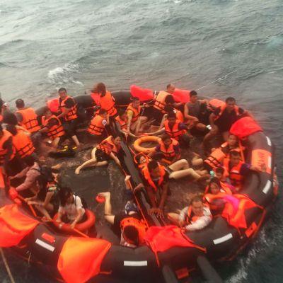 Turistiveneen kaatumisesta pelastettuja ihmisiä nostetaan pelastuslautalta kalastusaluksen kyytiin Phuketin edustalla. Valtaosa ihmisistä oli kiinalaisia turisteja.