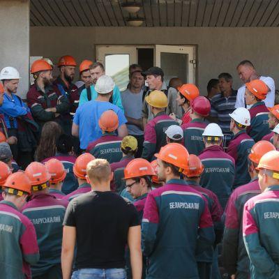 Kaivosmiehiä kypärissään tuotantolaitoksen edustalla
