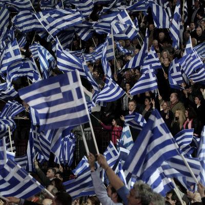 Greker viftar med falggor under valmöte inför det grekiska parlamentsvalet 25.1.2015