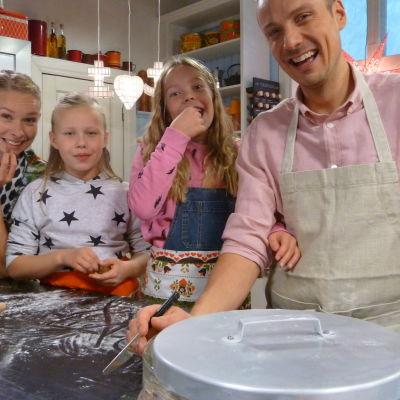 Programledarna Hanna Enlund och Jontti Granbacka bakar pepparkakor med flickorna Tuva och Joanna.