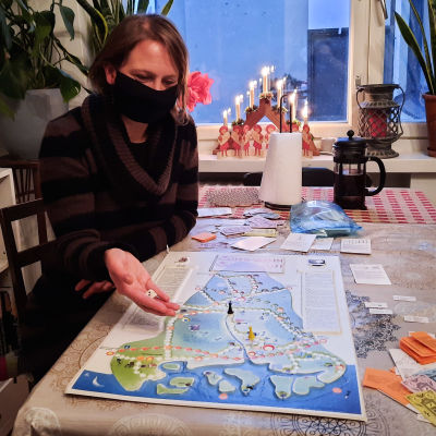 Kvinna i svart munskydd sitter vid köksbord och håller på med att kasta en tärning ovanpå en spelplan föreställande Sibbo.