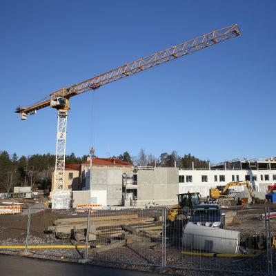 Två lyftkranar på en byggarbetsplats. Halvfärdiga byggnader i betongelement.