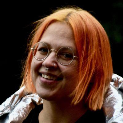 Bild på kvinna i silvrig jacka som ler mot kameran. Personen är Catariina Salo.