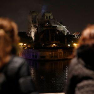 Notre-Dame i Paris brinner. Två kvinnor ser på branden.