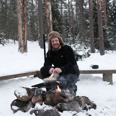 MIkko Peltola valmistaa ruokaa nuotiolla Nuuksiossa.