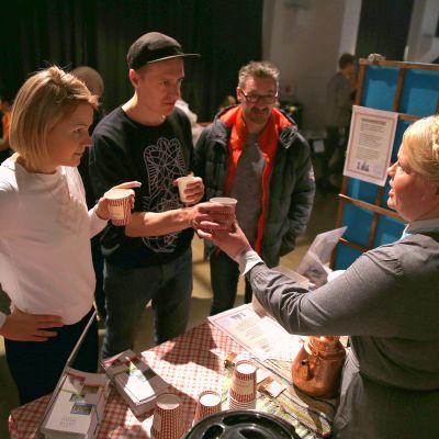 Helsinkiläiset Suvi Rantonen ja Aapo Kojo maistoivat kahvinvastiketta Helsinki Coffee Festivalilla lauantaina. Tarjoilijana Lottamuseon lottakanttiinin emäntä Tuija Keskinen.